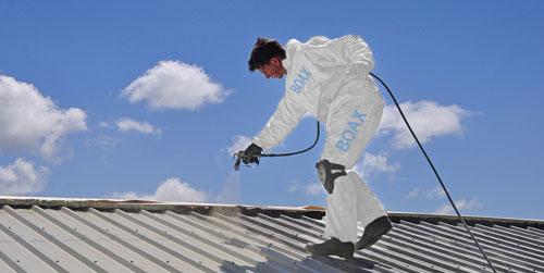 Man som utför fastighetsskötsel uppe på ett tak